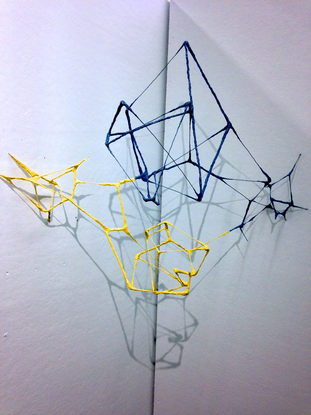 Inversion, hot glue, wire, and spray paint This corner-mounted wall piece attemps to create a mini-environment through emulating shifting geormetric forms and voronoi map fractals.   The end result is a sculptural duality through which shadows play with physical wire patterns.