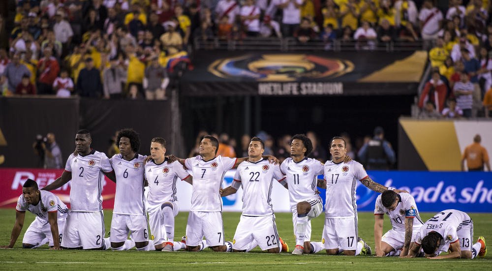 Colombia teammates kneel together as they wait for the penalty kicks to decide the game.