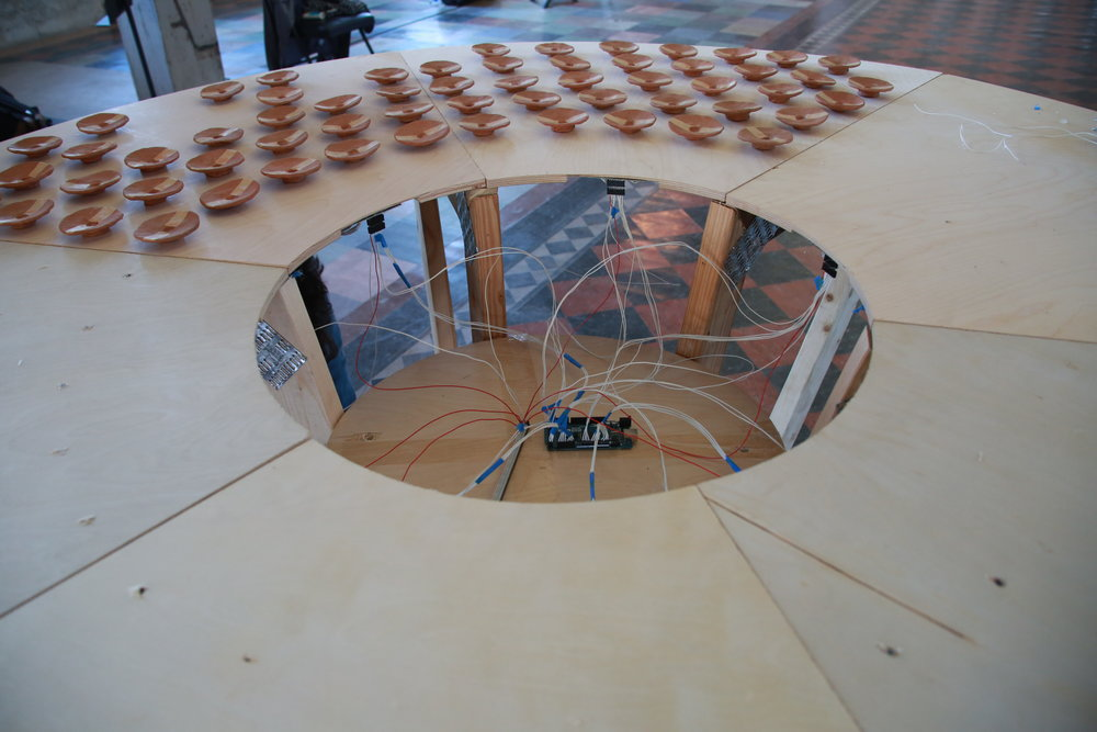 The interactive table contains 200 sensors which measure the presence of each handmade ceramic cup. When a cup is removed, that information is logged and sent to a server which communicates with the resonant sculptures on stage as well as the musician's tablet screens which display musical cues.