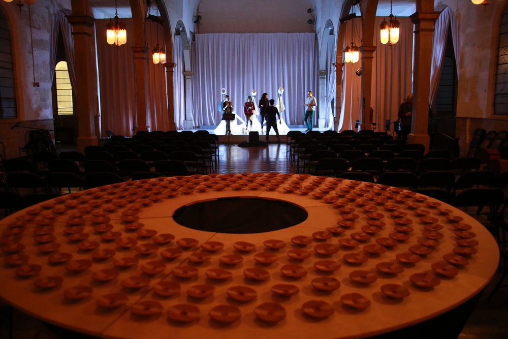 The audience is greeted by an interactive table displaying 200 handmade ceramic cups, and invited to take one of the cups. When a cup is removed, 1) the sculptures on stage resonate audibly in the space and 2) the music of the 2nd movement is arranged generatively.. but how? See the  Design & Tech.