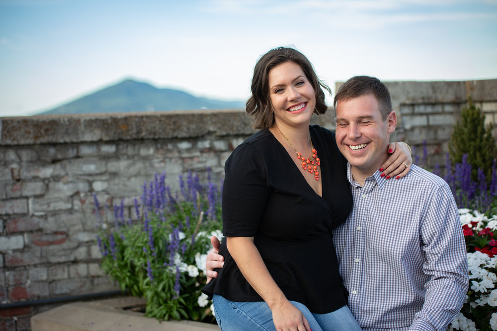 center-in-the-square-downtown-roanoke-urban-rooftop-engagment-wedding-couple-love-mountain-flower-bed-sitting-laughing-smile
