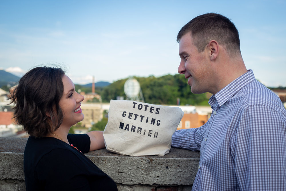 center-in-the-square-downtown-roanoke-urban-rooftop-engagment-wedding-totes-getting-married-love-couple-smile-laughing