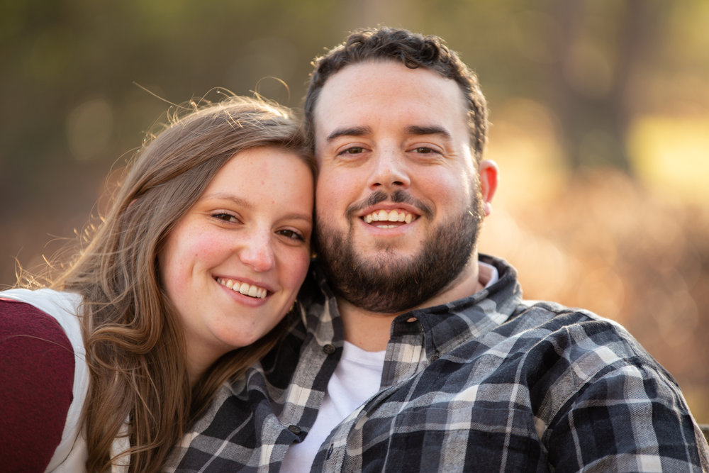 Fall-Laughing-together-bench-trees-duck-pond-virginia-tech-blacksburg-roanoke-engaged-warm-at camera-smiles-natural-candid