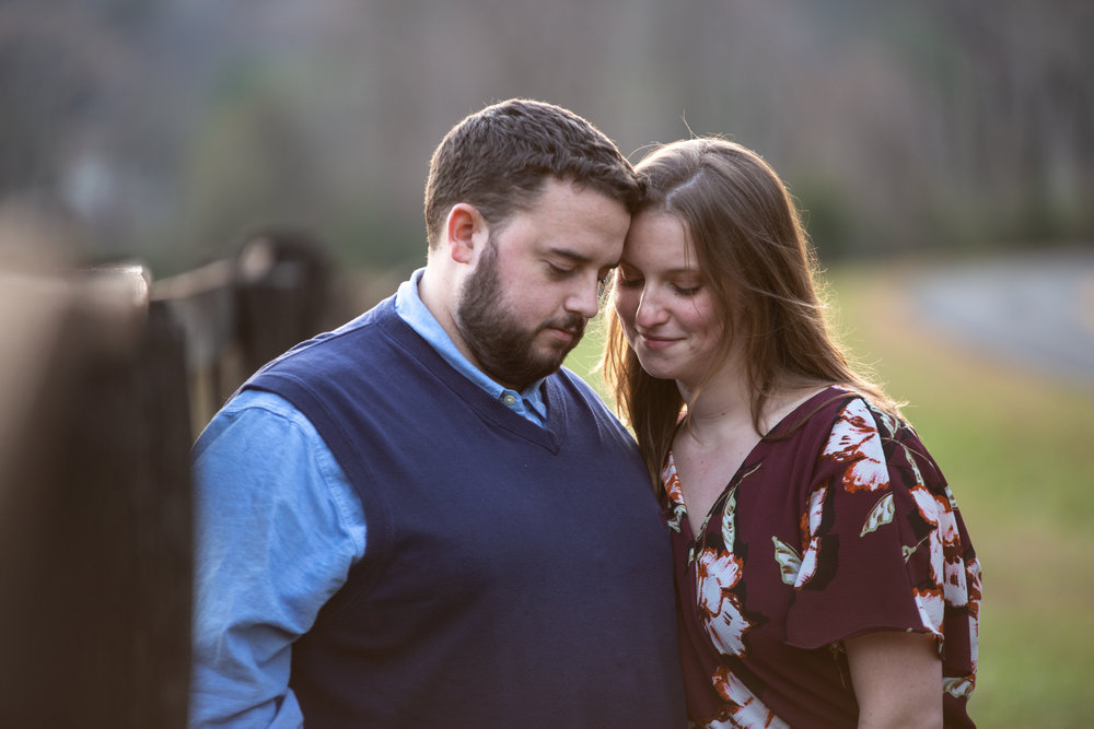Blue-Ridge-Parkway-Fall-Sunset-couple-engaged-mountains-love-together-fence-roanoke-engaged-beauty-virginia-photography-nature-candid-heads-together