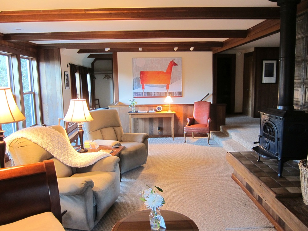 The Barn Loft's living room is spacious and comfortable with a stove-type wood fireplace.