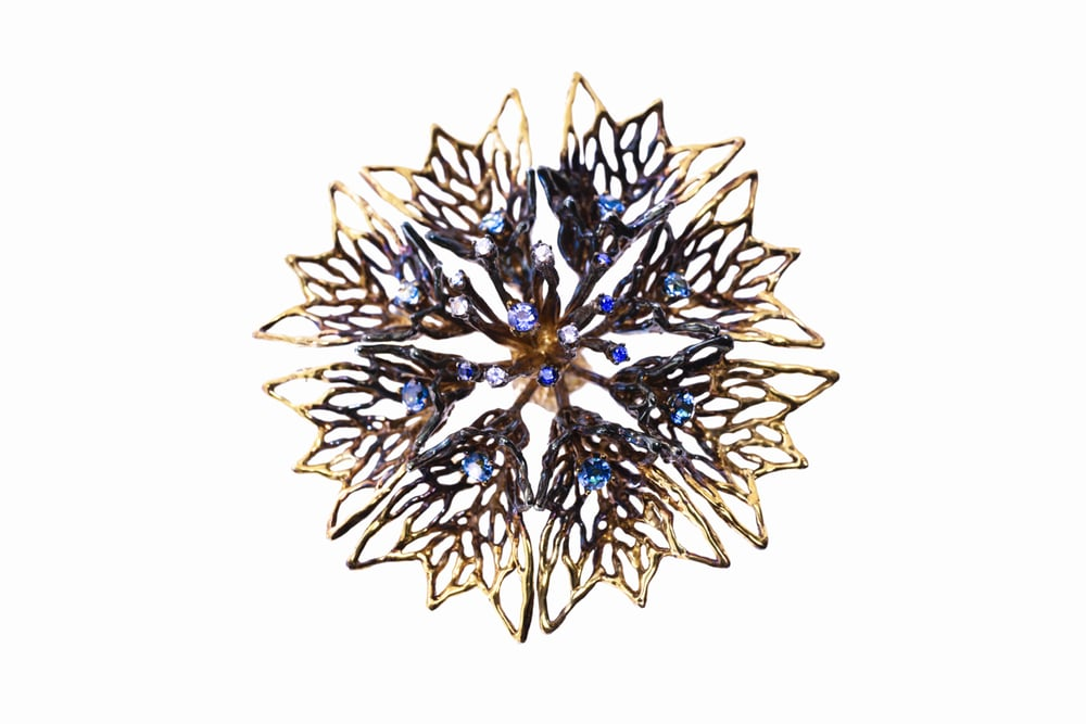 Central flower of Cerulean Odyssey. An outer halo of topaz surrounds inner settings of white and blue sapphires with a larger Australian blue sapphire at the centre