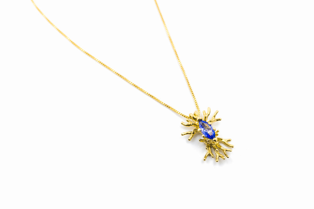 18ct yellow gold branches surround and hold a marquise cut tanzanite.