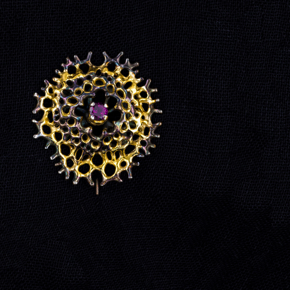 Enclosed Radial Brooch | Sterling silver, garnet, gold vermeil, patina.