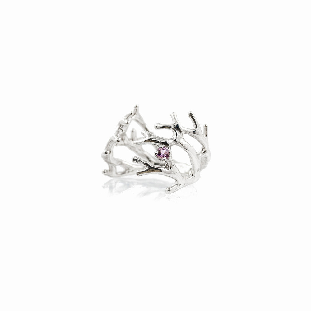A silver dendrite ring with a pink sapphire set within it's branches.