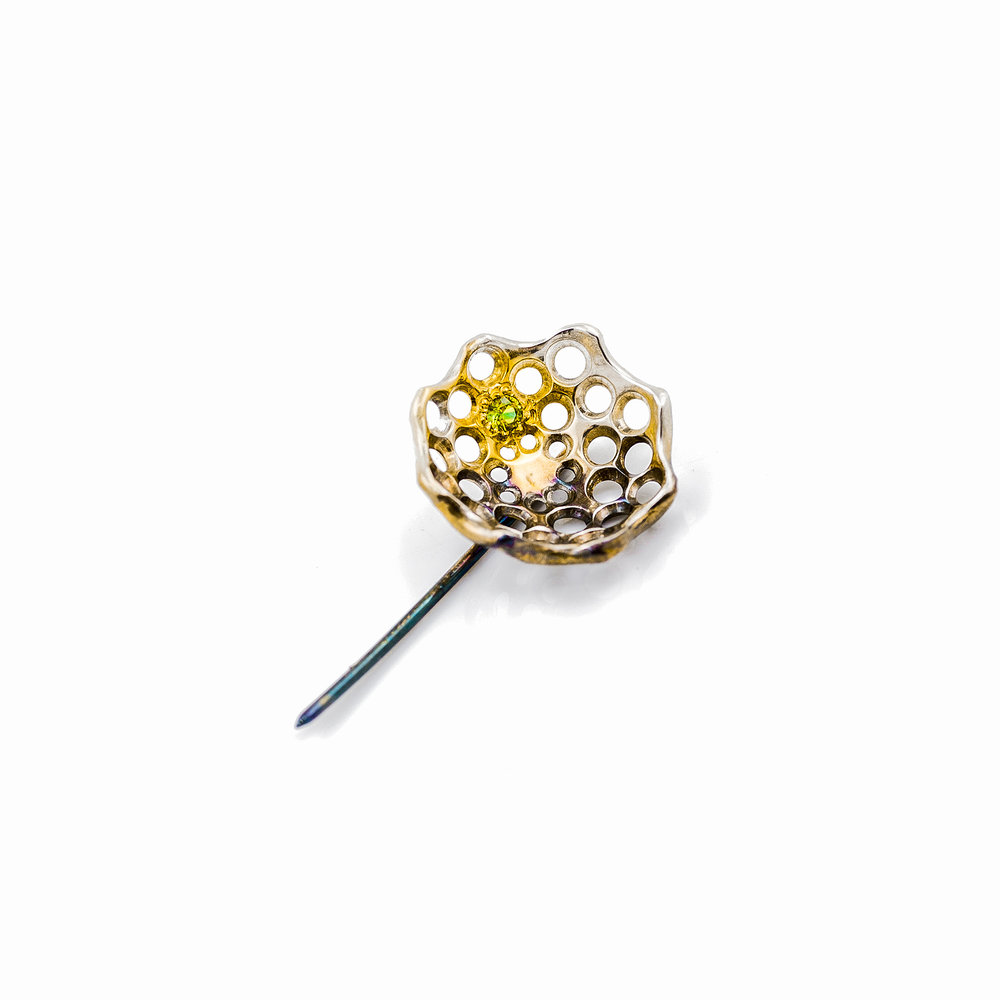 Silver pin with gold vermil and oxidate patina. Set with a green Australian sapphire.
