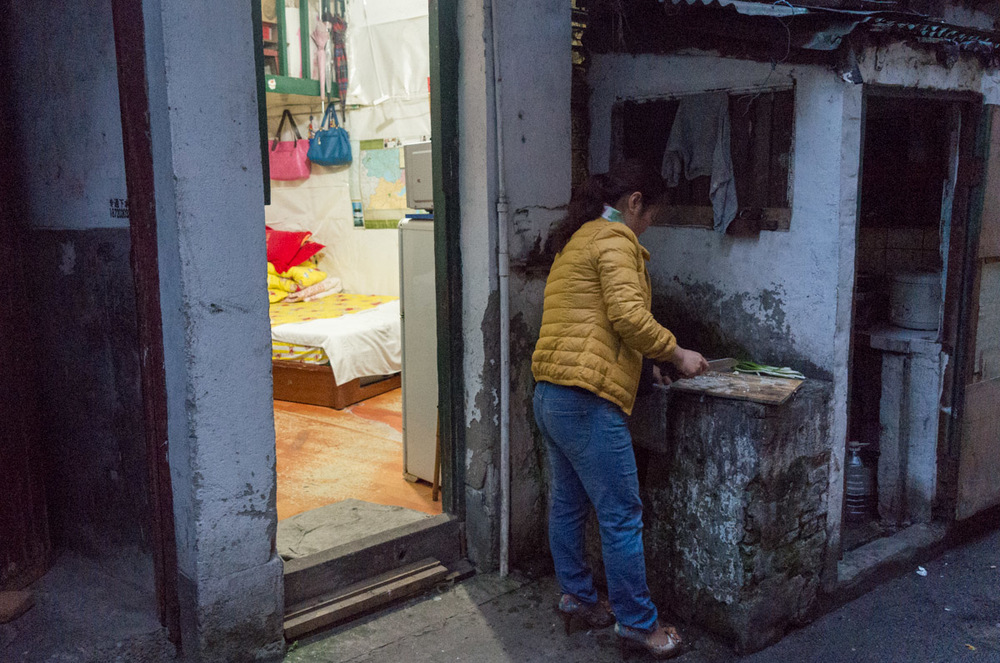 Unfortunately this is how a lot of poor people live in Shanghai , here the lady is preparing food in her outside 'kitchen' next to the only room she lives in with her family.
