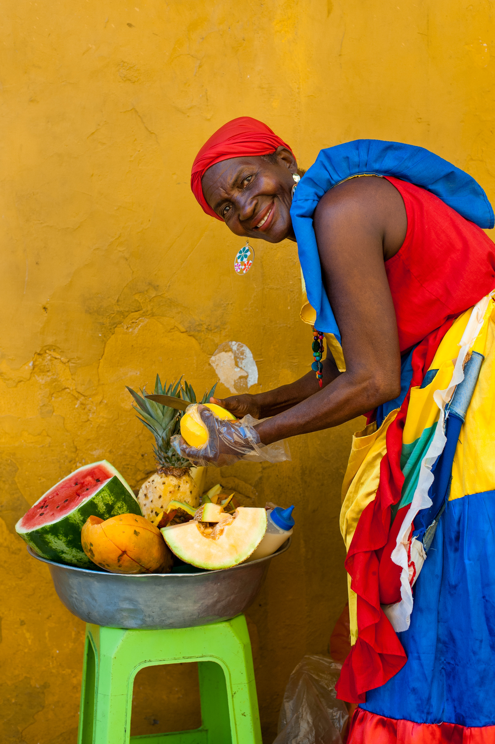 Colombia Woman dressed in traditional clothes cutting and selling fruit in the colorful old town of Cartagena. Colombians are blessed with a fertile country and an eye-popping array of tropical fruit.