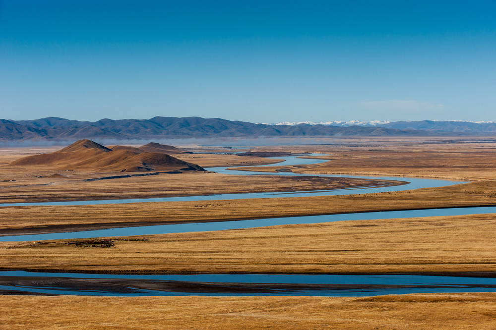 China At 5,464 kilometers, this is the second longest river in China (after the Yangtze) and the sixth-longest in the world. At sunrise the still water reflects the deep blue sky like a mirror. The tiny black specs on the grasslands are Yaks grazing.
