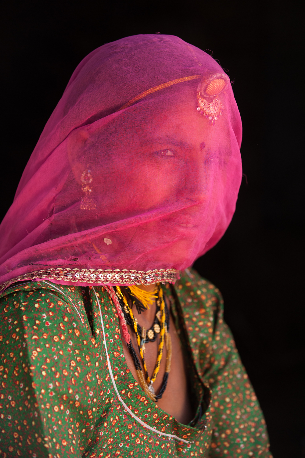 India A Rajasthani woman wearing traditional jewellery and a veil called a Ghoonghat