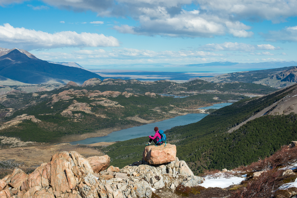 Argentina A woman takes a break from hiking the trail in El Chalten National Park in Patagonia in Argentina to take in the view. Lake Viedma is visible in the distance.