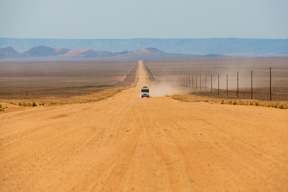 Namibia A jeep on a long sandy road in southern Namibia leaves a trail of dust