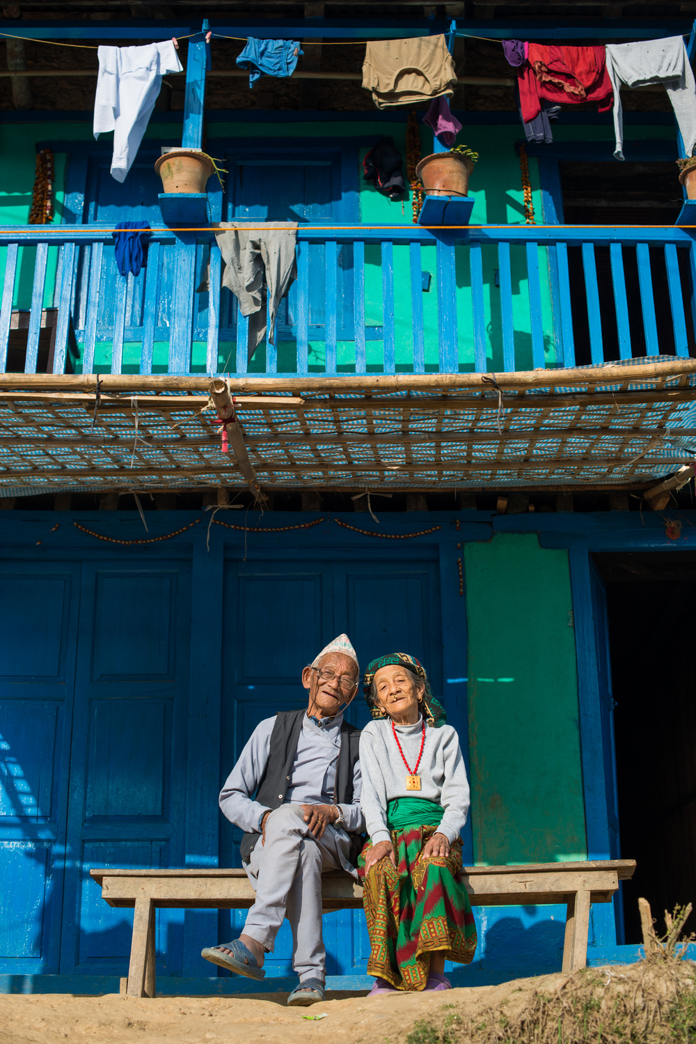 Nepal A old Nepali couple wearing traditional dress sit outside their house in Diktel
