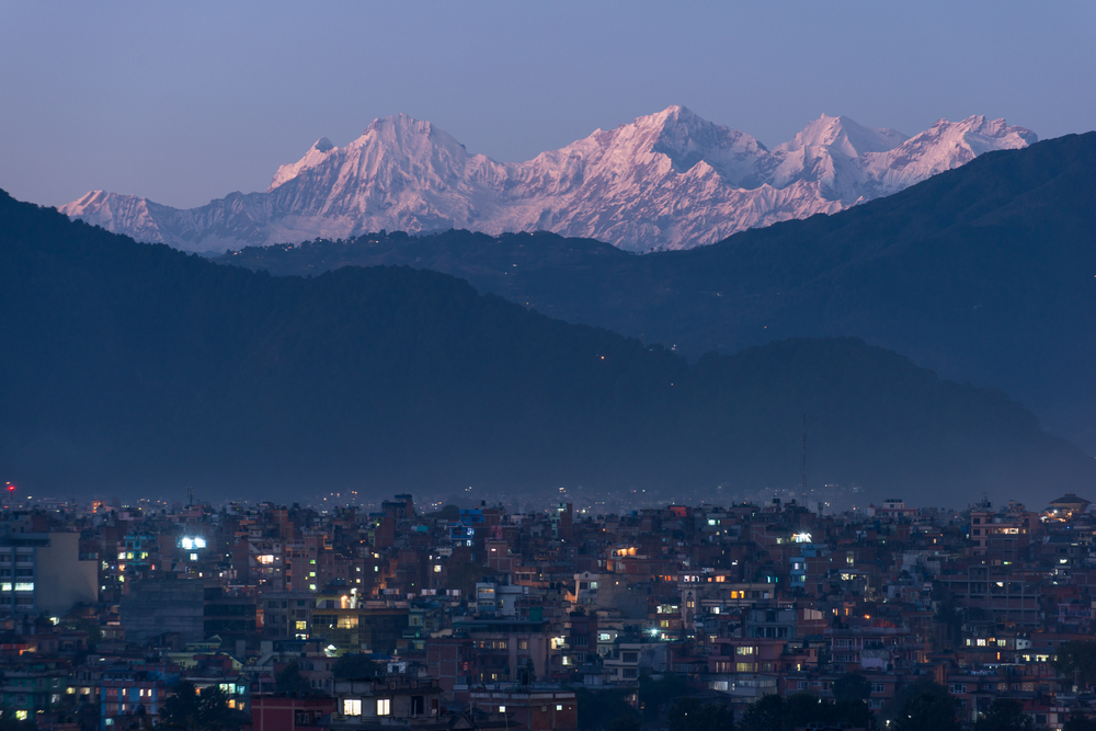 Nepal - Kathmandu   It was during the week of the 2013 elections when strikes (bandhs) enforced a week-long driving ban in the city. By the end of the week Kathmandu was unusually clear of pollution. That combined with a particularly clear night and a full moon provided me with this unique opportunity to photograph Kathmandu at night with the Ganesh Himal clear in the background.