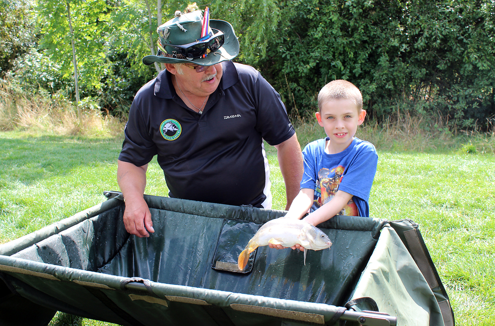 PAA coach Dave milton helps a young lad with his first mirror carp of the day