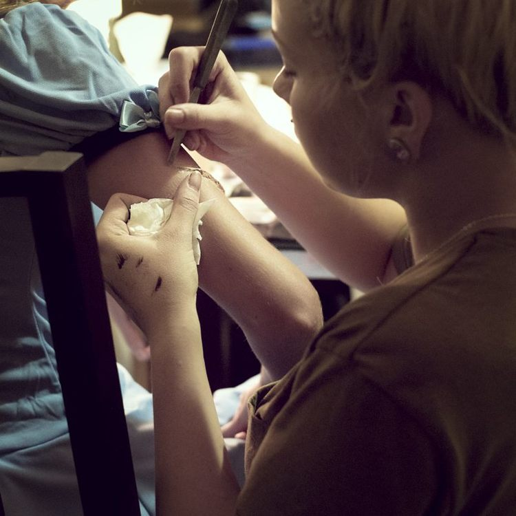 Amy applying FX wax to sculpt the gash in Ash's arm.