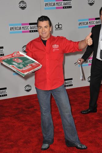 Papa John of Papa John's Pizza holding a pizza box with the NFL logo