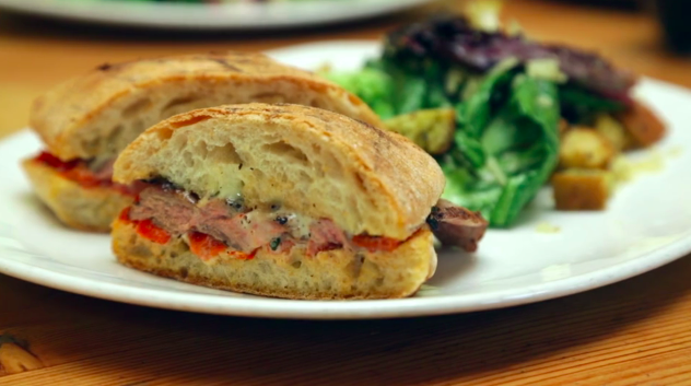 Steak sandwich with roasted red peppers, housemade aioli on a toasted ciabatta roll
