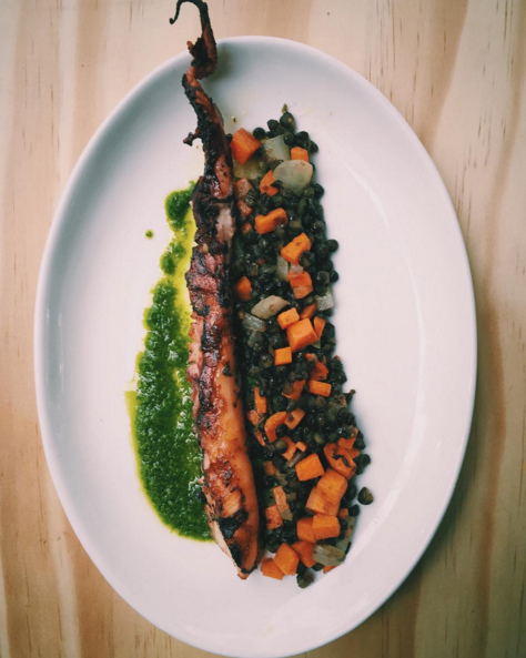 Charred octopus with black lentils and green harissa at Cava Mezze  | Instagram @cavamezze