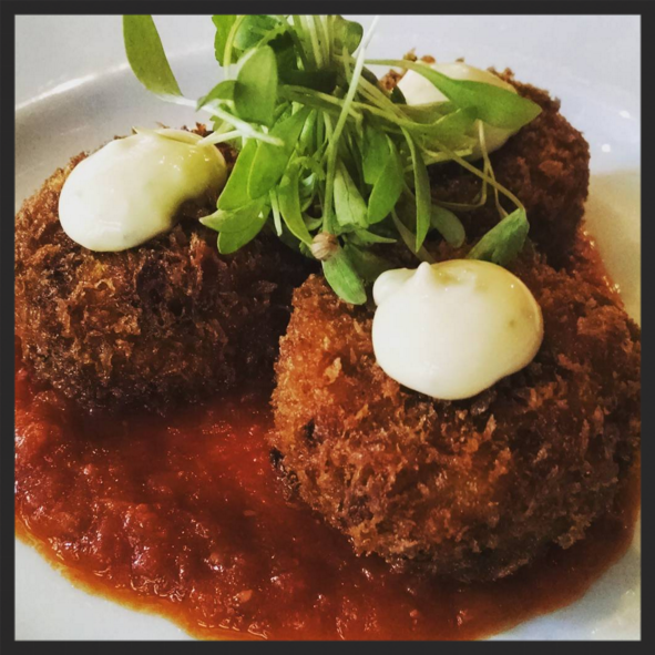 Paella Arancini: grilled shrimp, chorizo, saffron rice, garlic aioli at Wright & Company | Instagram @wrightdetroit