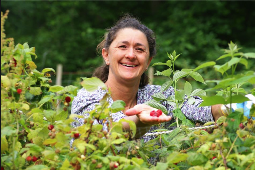 Shelly in her garden with raspberries!
