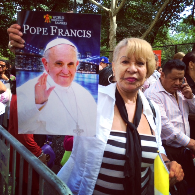 Woman holing up Pope poster entering Central Park.