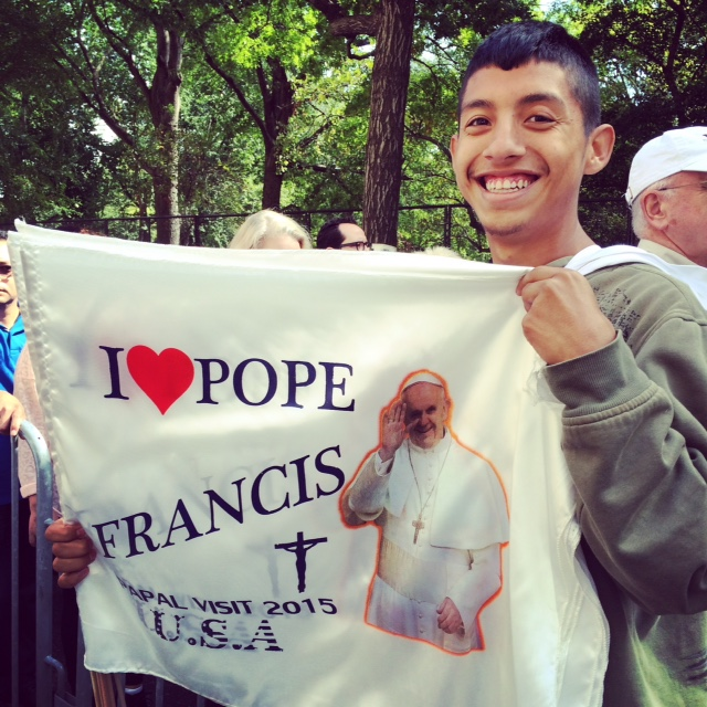 A teen seeling Pope flags
