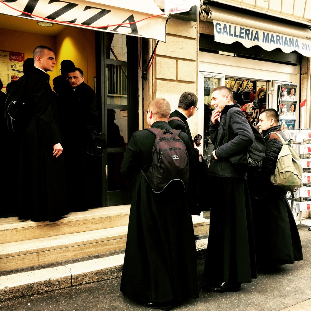 Priests stop for pizza near Vatican in Rome, Italy