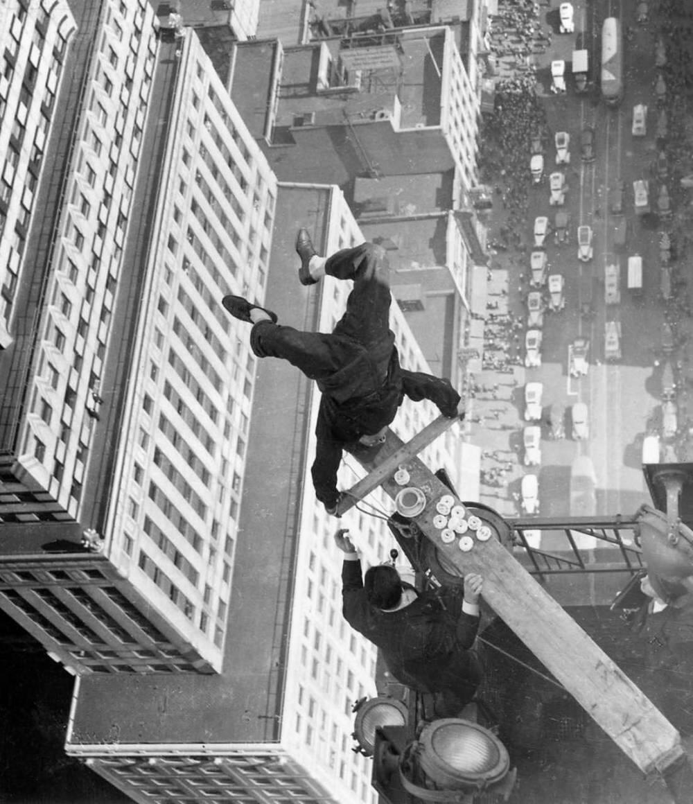 Harold Lloyd, a silent film comedian, performs a headstand on the edge of a skyscraper. 1930s.