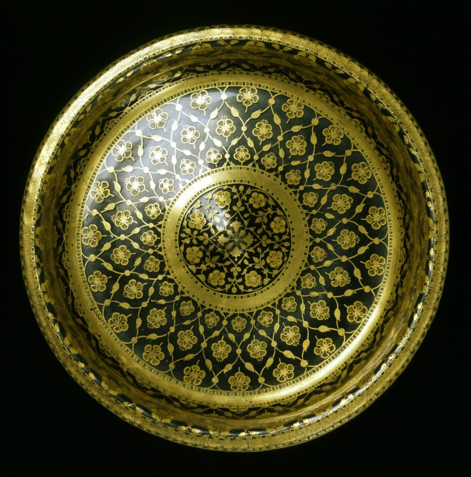 D ish, colorless glass, decorated with enamel and gilded. India, Mughal; c. 1700. The flowers on the dish were contoured on the inside with gold and filled in with red and yellow enamel, while the outside was painted solely in yellow. This produces a kind of three-dimensional effect that is characteristic of Mughal glass art with painted decoration. Photo: The David Collection