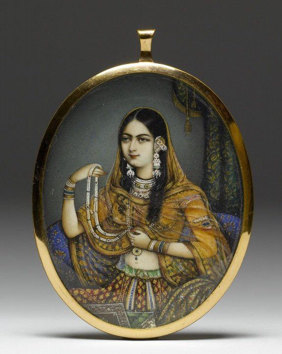 Miniature portrait pendant. Watercolor on ivory, gold, glass.  1830-1850, India. In this instance, an artist from Delhi has portrayed a  courtesan dressed as a princess wearing elaborate Mughal gold and  gem-set jewelry. Photo: The Walters Art Museum