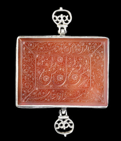 A Qajar silver-mounted inscribed carnelian Armband (bazuband), Persia, 19th Century. Rectangular, engraved with a central cartouche containing inscriptions on a ground of floral interlace, surrounded by four panels containing inscriptions on a ground of scrolling floral vines, the silver mount with two hinged suspension loops decorated in openwork with foliate motifs  8 x 6 cm. Image: Bonhams