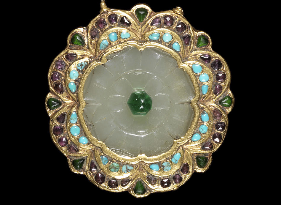 A Qajar gem-set and gold mounted jade Plaque. Persia, 19th Century. In the form of a flowerhead, the jade carved with petals and surmounted by a green glass bead, surrounded by a stepped gold mount set with turquoise and paste, small gold attachment loop to side and two jade attachment loops to reverse. 5.8 cm. diameter. Image: Bonhams