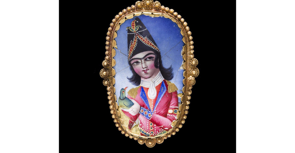 A Qajar enamelled plaque mounted as a gold brooch. Persia, 19th Century. Of curved oval form, the polychrome enamel plaque depicting an elegantly dressed courtier holding a parakeet, the yellow gold mount decorated in filigree. Image: Bonhams