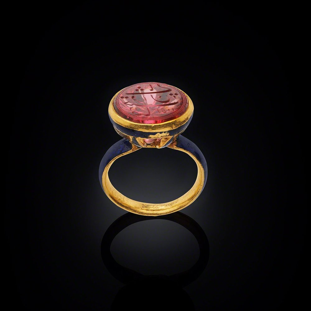 """Ring with Shah Jahan's Spinel    North India, the spinel dated AH 1053 (AD 1643– 44); the ring, c. 1900Gold with enamel, the spinel inscribed in Persian: Sahib qiran-i thani (""""Second Lord of the Auspicious Conjunction"""")    Dating from 1643, this spinel is engraved on the reverse """"Sahib qiran-I thani"""" which translates as """"Second Lord of the Auspicious Conjunction"""", the title of Emperor Shah Jahan who ruled 1628 - 1658. The title was chosen by Shah Jahan himself in reference to Timur (Tamerlane), the Mughals' dynastic ancestor, who bore the title """"Lord of the Auspicious Conjunction"""". It is most likely that the engraving on the spinel was also the sovereign's personal seal. Image courtesy: © The Al Thani Collection"""