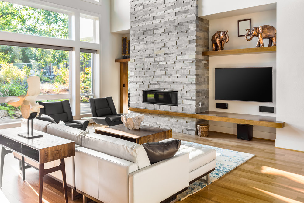 Beautiful living room with hardwood floors and tall fireplace in new luxury home