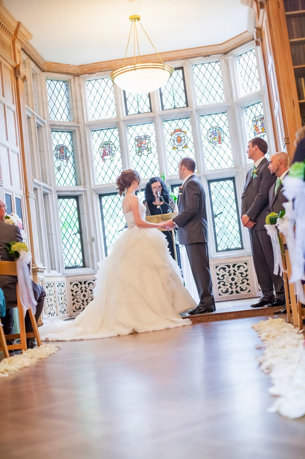 Ceremony in the historic library at The Morton Arboretum. Ivory rose petals line the aisles and green hydrangea as aisle markers. April is wearing a Justin Alexander gown.