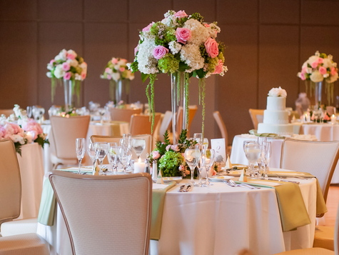 Tall centerpieces with hydrangia and roses. Ivory tablecloths with green napkins. Mint green wedding cake.
