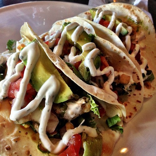 Trio grilled chicken tacos. Tequila honey-lime marinated chicken over lettuce, topped with roasted corn salsa fresh avocado and lime-cilantro crème