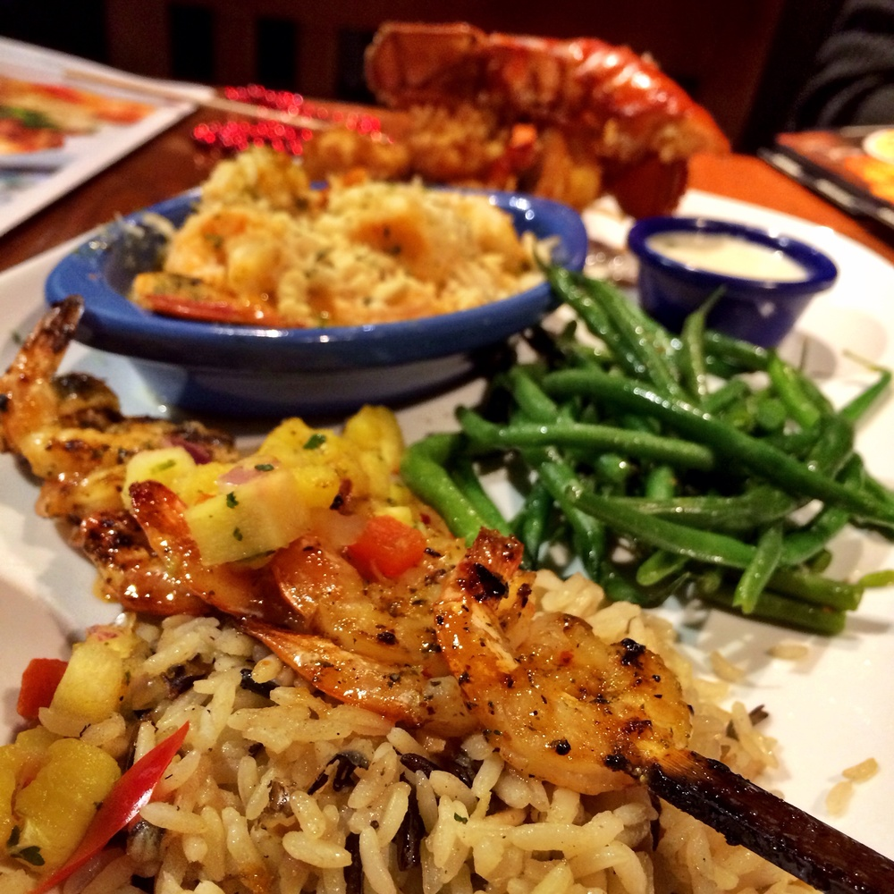 Seaport Lobster & Shrimp. A wood-grilled split Maine lobster tail, savory garlic shrimp scampi and a skewer of garlic-grilled shrimp. Served with wild rice pilaf