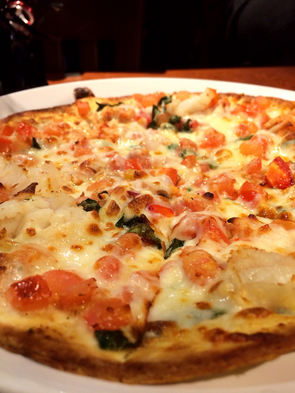 Lobster Pizza. A crisp thin-crust pizza topped with langostino lobster meat, melted mozzarella cheese, fresh tomatoes and sweet basil
