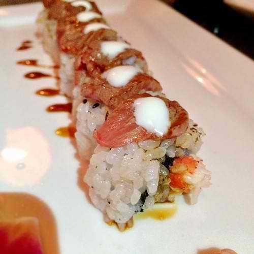 Louis Vuitton @kabooki_sushi King crab meat, tempura flake, asparagus, orange chili sauce topped with blow torched wagyu beef, Italian black truffle salt, creme fraiche, drizzled with faux nagi sauce