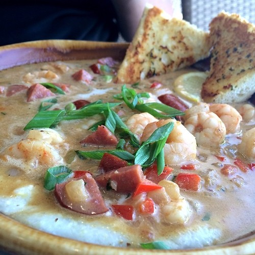 Shrimp 'n Grits (  @BrokenEggCafe) Shrimp & Andouille sausage sauté, spicy low country reduction sauce, sautéed red bell peppers & onions on creamy cheese grits with garlic French bread