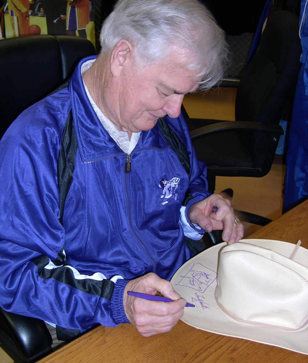 Tex Winter signs a cowboy hat when he came to visit Kansas State University, where his coaching career began. He is loved by his fans for who he is as well as his sixty-three years of coaching. He changed how basketball is played.
