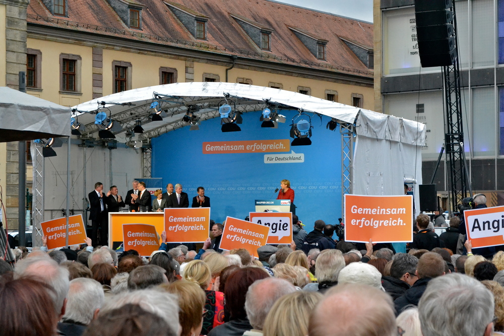 Angela Merkel speaking from the podium. Note all the grey hair in the crowd....