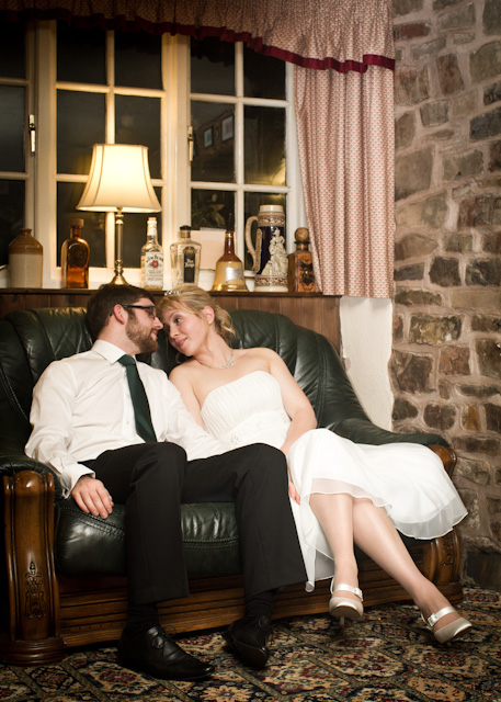 Jess and Martin relax on a sofa by the fire at their Wedding Reception at the Thelbridge Cross Inn in Devon near Crediton.